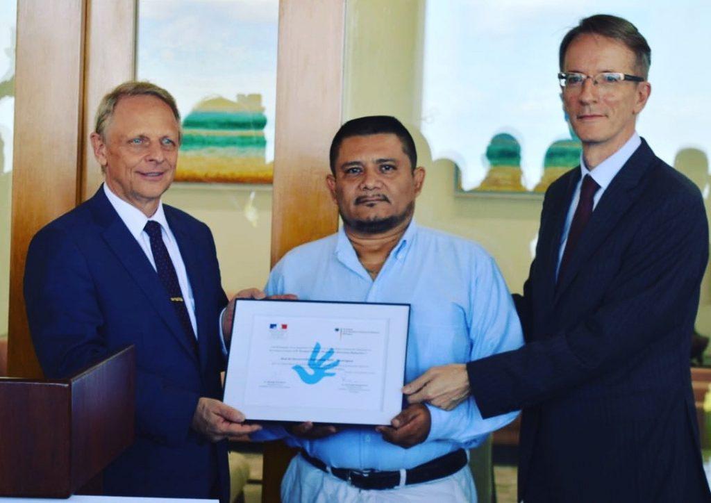 Juan vom RDS nimmt den Deutsch-Französischen Menschenrechtspreis vom Deutschen Botschafter Dr. Christoph Bundscherer und dem französischen Botschafter Philippe Létrilliart entgegen